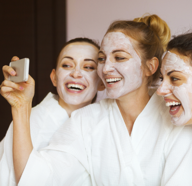 Three Women in White Robes and Face Masks Laughing and Taking a Selfie