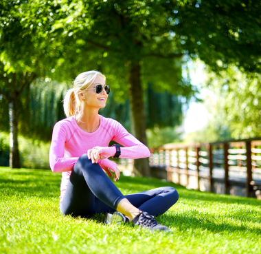 Woman wearing workout clothes sitting in a park checking her watch