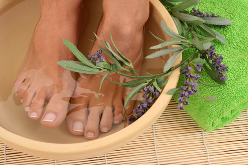 Bare Feet with a French Pedicure Soaking in a Bowl of Water