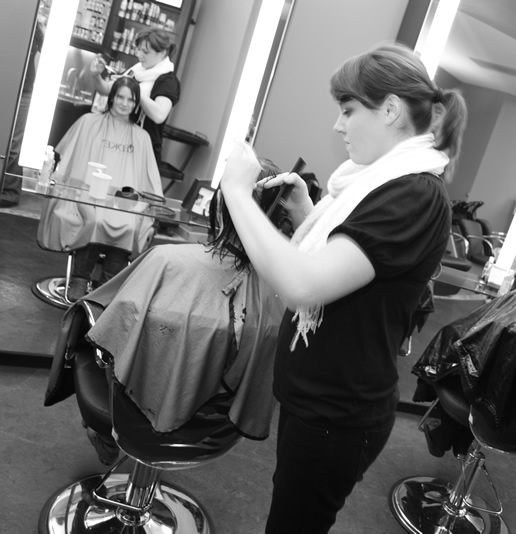 Hair Stylist at Complexions Salon in Saratoga NY Performing a Woman's Hair Cut