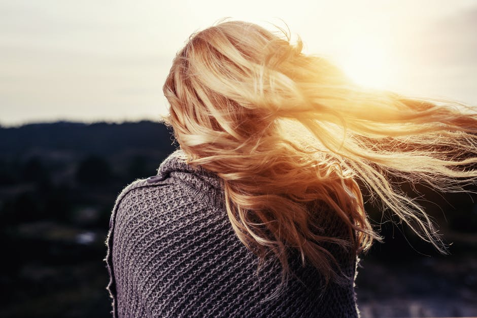 Woman with Sunlight Reflecting Off Her Blonde Hair Blowing in the Wind