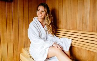 Woman in Spa Robe Sitting in a Sauna