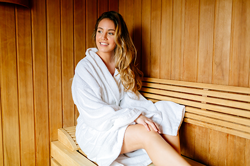 Woman in Spa Robe Sitting in a Sauna