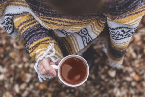 Woman Wrapped in a Blanket Holding a Hot Drink in a Mug