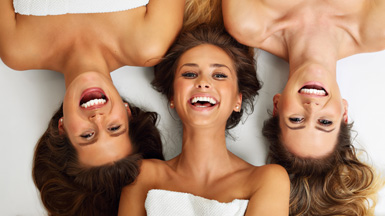 Three Young Woman in Spa Towels Lying Down & Laughing