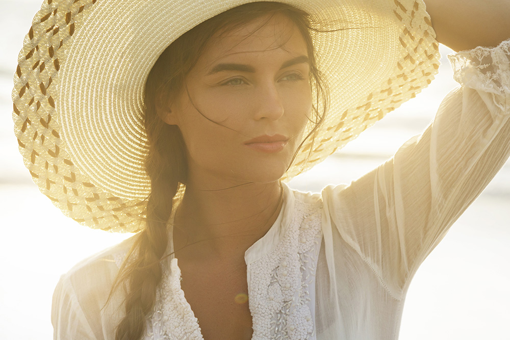 Woman Blocking the Sun with a Wide-Brimmed Straw Hat